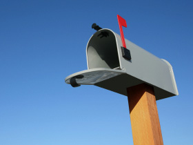 An open residential mailbox with flag up